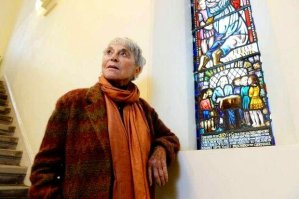 Professor Eva Haller, who said she owed her life to Jane Haining, stands by a commemorative stained glass of her mentor.