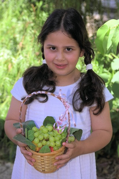 6_A girl in Jerusalem holds a fruit offering (Bikkurim) on Shavuot holiday