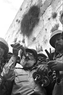 Army Chief Chaplain Rabbi Shlomo Goren stands surrounded by IDF soldiers and blows the shofar in front of the Western Wall in Jerusalem on June 7, 1967. (Photo by Government Press Office, Israel)
